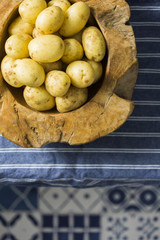 Salad potatoes in a wooden bowl on a table with blue cloth