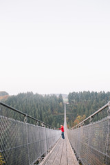Man exploring and standing on a long bridge in nature