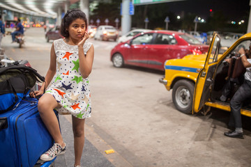 Teenage girl awaiting outside airport with luggage
