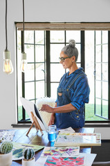 Mature woman artist with grey hair in her art studio in California painting a watercolor