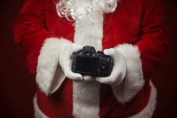 Santa Claus using holding in hands DSLR camera showing screen display. Closeup of creative ideas work, taking shooting images. Happy Christmas and New Year celebration design background.