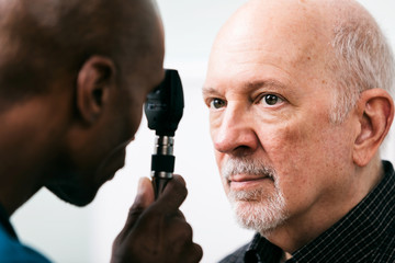 Exam: Doctor Uses Ophthalmoscope To Check Eyes Of Patient