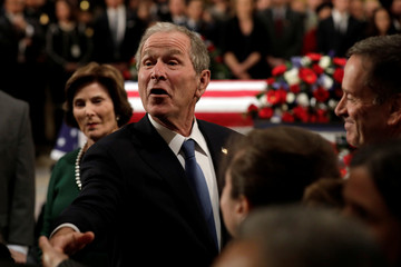 Former President George W. Bush greets visitors who came to pay their respect at the flag-draped casket of former U.S. President George H.W. Bush