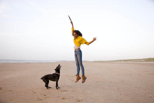 young woman with black dog on the beach, jumping