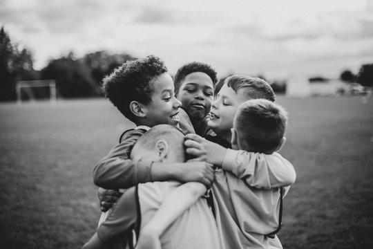 Junior football team hugging each other