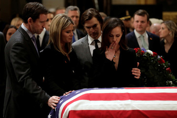 Family members stand at the flag-draped casket of former U.S. President George H.W. Bush