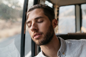 Young adult male relaxing in back of car while on road trip