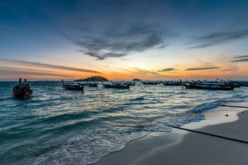Silhouette of Traditional Thai fishing boats or long tail boats parking at the fishing boat bay at tropical sunrise.
