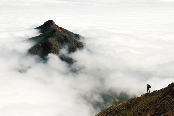 An adventurous male traveler looks out over a mountain peak rising above a thick layer of clouds in Chile's Parque Nacional La Campana