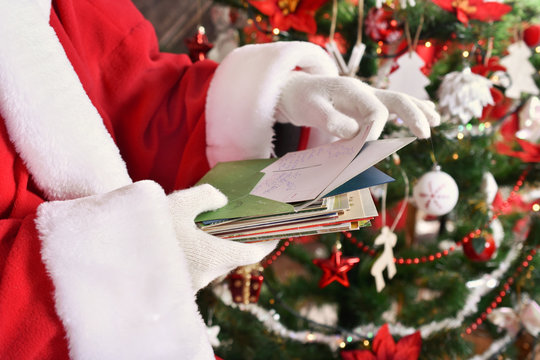 santa claus reading letters from children in front of christmas tree