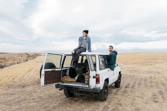 Lifestyle image of male and female sitting on top of suv truck in field on off road adventure