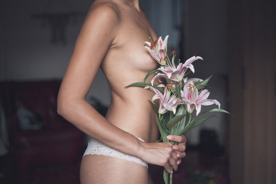 Anonymous naked woman covering herself with flowers