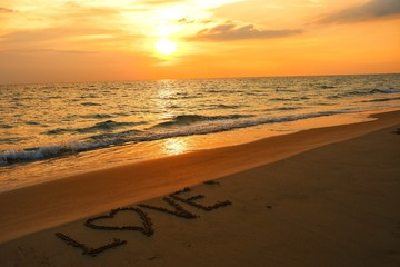 Marry concept, love heart shape handwriting on sand beach in sunset.