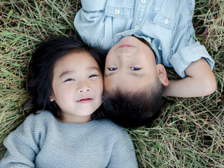 Little Girl and Boy Laying in Grass