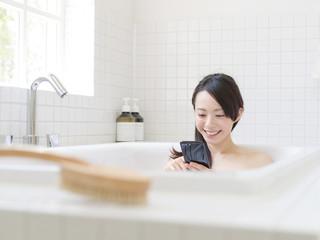 スマートフォンを持って入浴する女性