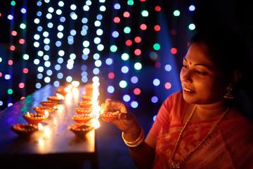 Woman lighting earthen oil lamps on Diwali