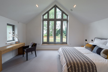 Modern bedroom with a large window at the apex.
