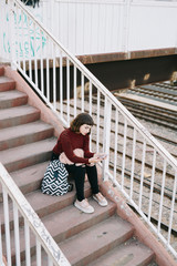 Woman on stairs using smartphone