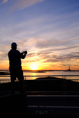 Person using phone to photograph sunset.