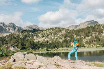 Blonde woman hiking in the pyrenees mountains on a bright summer day