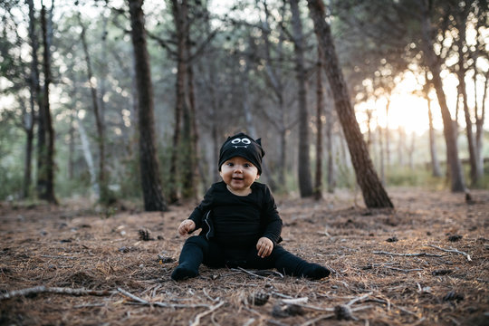 Lovely baby in bat costume in forest.