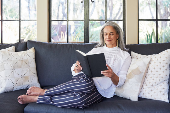 Mature woman with grey hair reading a book on sofa in living room