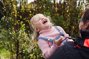 Woman and toddler girl laughing together