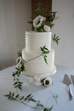 White icing wedding tiered wedding cake with vines and simple white flowers