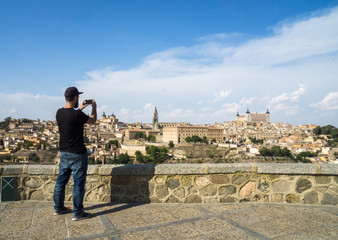Man taking a photograph with his smartphone to  the old city