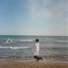 A woman watching dog swimming at the sea