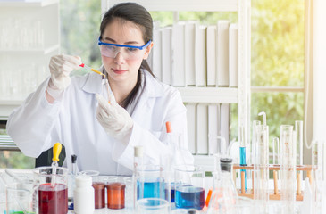 Scientist beautiful woman working putting medical chemicals sample in test tube at laboratory