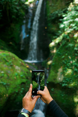 Taking a photograph of a waterfall with a cell phone.