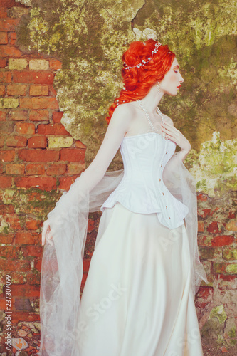 b7e249bf4a5 Victorian redhead princess with hairstyle in corset. Fabulous fairytale  queen with historic hairdo against stone wall. Victorian doll.