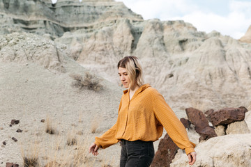 Lifestyle Portrait of young fashionable female young adult in unusual unique high desert environment landscape eastern oregon