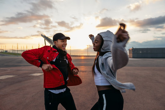 Couple dancing outdoors during sunset