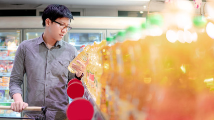 Young Asian man with eyeglasses choosing vegetable oil from product shelf in supermarket. shopping lifestyle in grocery store concept