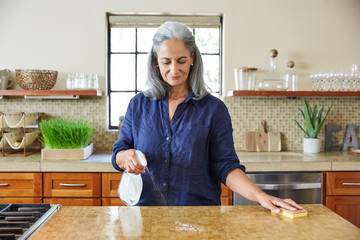 Mature woman cleaning using all natural cleaning products at home