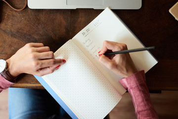Top view of woman's hands writing to-do's list in notebook.