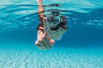 Underwater view of a female tourist snorkeling in clear water in