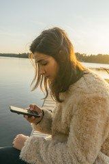 Girl Checking her Phone on a Dock's Lake at Sunset.
