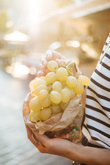 Unidentified person holding cluster of grapes and ready to consume some of it