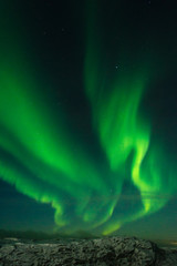Beautiful stripes of the northern lights, aurora in the night sky above the snow covered hills.