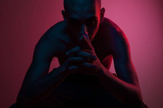 shirtless man under neon lights