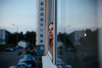 Woman waiting and thinking at window