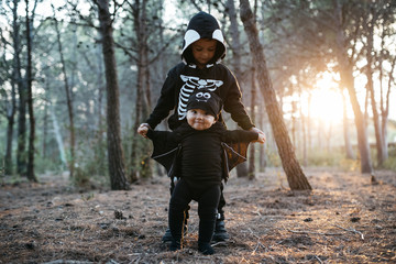 Brothers in halloween costumes in forest in evening.