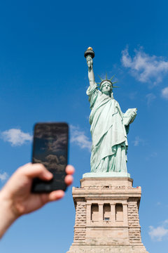 tourist taking picture on mobile phone of Statue of Liberty