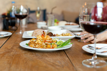Famous Pad Thai noodles with shrimps and glass of red wine on wooden table.