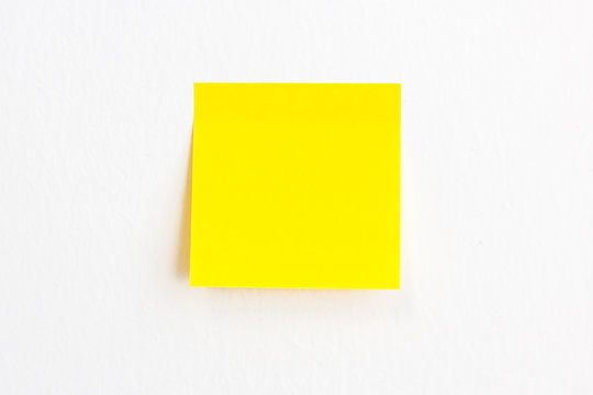 Yellow post it paper note on a white wall background with empty space.