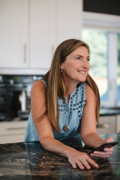 Healthy, active woman enjoying mobile phone at kitchen counter b