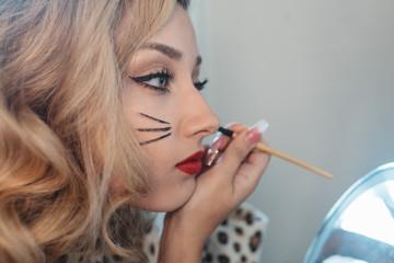 A teenage girl applying her makeup for halloween